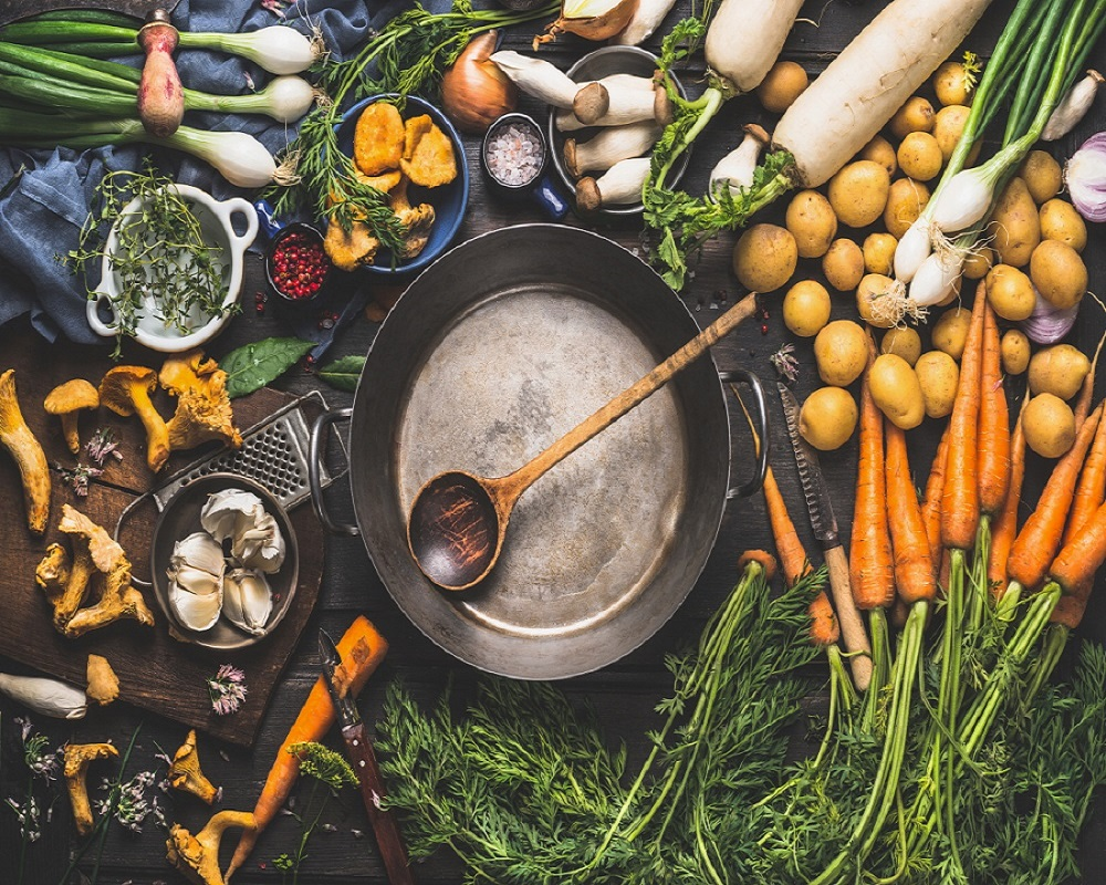 Various organic vegetables ingredients around empty aged cooking pot with wooden spoon on old kitchen table, top view